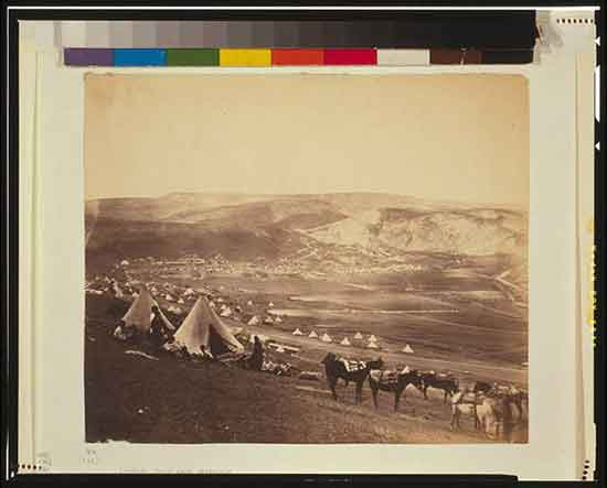 Cavalry camp near Balaklava. Military encampment showing conical tents, people, and horses, with mountains in the background.