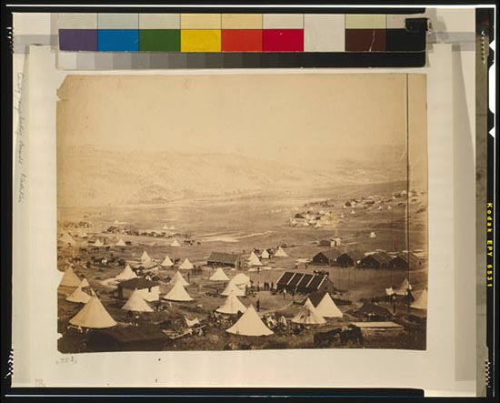 Cavalry camp, looking towards Kadikoi. View of encampment showing bell tents, huts, soldiers, and horses.